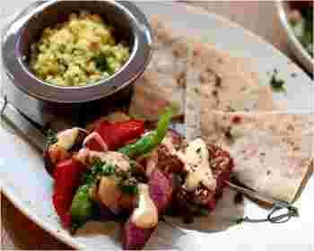 「スブラキプレート」の一例。スパイシー風味のテンペや豆腐、季節野菜の串焼きとクスクス。ピタパンつき。