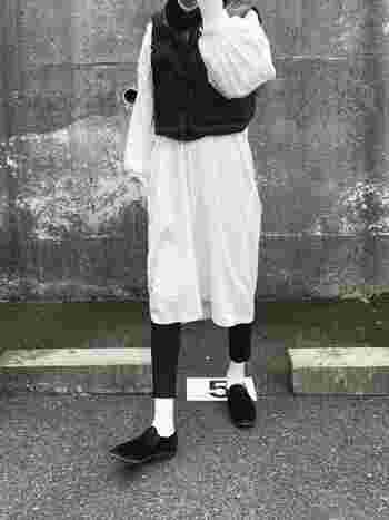 白黒、白黒...とオセロのように重ねたレイヤードスタイル。コットンワンピースにダウンベストを合わせる技が新鮮!
