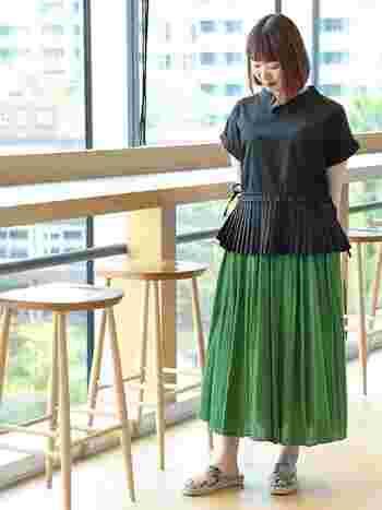 愛らしい形の黒シャツ。明るいグリーンのスカートで華やかさとコーデにアクセントをプラスして。北欧ライクなカラーリングに、パイソン柄のサンダルでスパイスを効かせましょう。