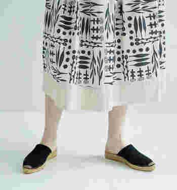 植物が描かれた印象的なプリントスカート。白地にネイビーのプリントなので、どんなアイテムにも合わせやすく着こなせます。裾の太いホワイトラインがアクセントで爽やか。民族的な要素を取り入れたスカートは、作家・小川温子さんのデザイン。