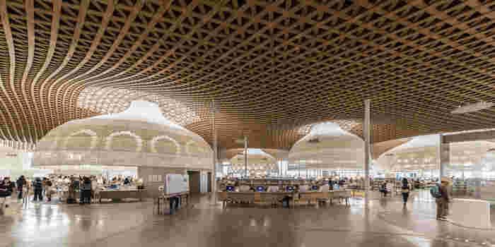 一階からつながるこの階段を登っていくと図書館へと続きます。図書館の天井からはお椀のようなものがたくさん並び、そこから漏れる光がやわらかな印象を作り出しています。