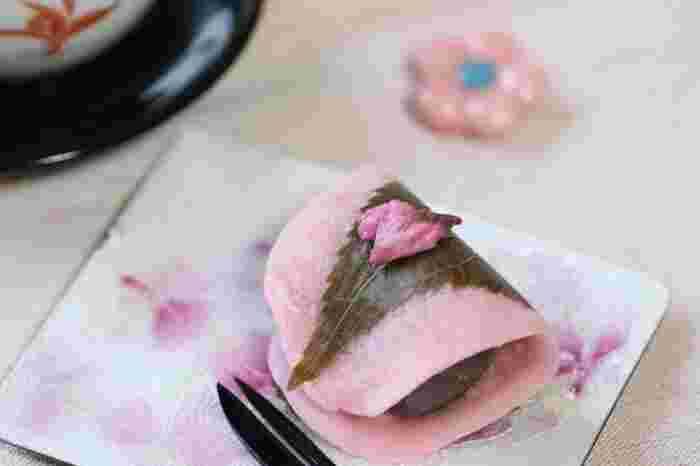 和菓子の世界では「桜」の名がついた上生菓子が数多くあります。その代表が「桜餅」ではないでしょうか?  こちらは、関東風の桜餅。発祥は江戸時代にさかのぼります。東京・向島にある「長命寺」の門前で和菓子屋を構えていた「山本屋」が、大川(隅田川)名物の桜並木の葉を塩漬けにし、餡を小麦粉で作った薄焼き生地で包んだものに巻いたとされています。  桜の香り豊かな上生菓子は、江戸の庶民にもとても人気が高く浮世絵にも描かれました。