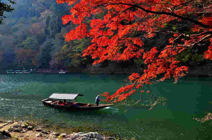 亀岡から嵐山の方に向かって約2時間かけて保津川を舟で下る「保津川下り」。舟が紅葉越しに保津川を行く様子は風流で印象的です。