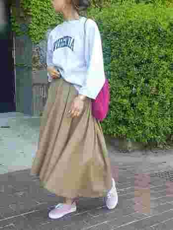 トレーナー×チノスカートのボーイッシュなスタイルは、ポップなピンク色のバッグが差し色になっています。足元には、同系色のライトピンクのスニーカーを合わせて、女の子らしさをプラスして。