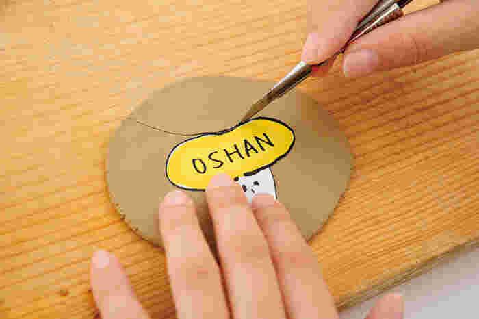 ①伸ばした陶土に作りたいブローチの型紙を置いて、型紙に沿ってカッターで周囲の陶土を切り取ります。文字や模様は、先のとがったものなどで型を付けておきます。