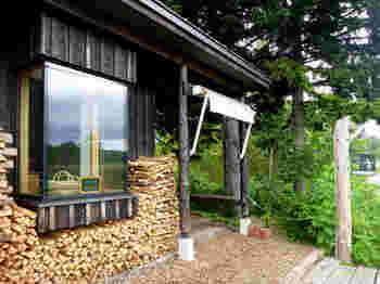 「Boulangerie JIN(ブーランジェリー ジン)」は、羊蹄山(ようていざん)の麓に位置する、虻田郡真狩村のベーカリー。自然豊かな環境でパン作りを行っています。お店の外には、パンを焼くための薪が積み上げられています。