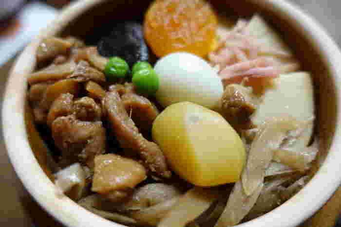 昭和33年に誕生した『峠の釜めし』は、秘伝の出汁で炊き上げたご飯の上に、ごぼうや椎茸、筍や鶏肉、栗や杏等など、様々な具がのせられた駅弁です。  丁寧に味付けされた具は、一つ一つ素材本来の旨味が感じられ、滋味豊か。ご飯との相性が抜群です。益子焼の土釜に入った佇まいも、ゆったりとした風情で、旅ならではの寛いだ気分で頂けます。