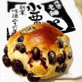 """「小西のパン」を代表するのは""""黒豆パン""""。丹波篠山の名産品、黒豆をたっぷり生地に入れた愛らしいパンです。頬張れば、柔らかな生地の甘味と、ホックリと炊かれた黒豆の滋味豊かな味わいが、口の中に広がります。"""