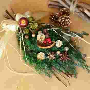プリザーブドフラワーのヒムロスギをベースにドライフルーツやスパイスを合わせたスワッグ。松ぼっくりやりんご、リボンなど、いろんな飾りを使った個性豊かな印象。グリーンやドライオレンジがふんわりと香るのも魅力です。