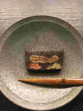 """wagashi asobiの商品は「ドライフルーツの羊羹」と「ハーブのらくがん」の2つ。もともと""""パンに合う和菓子""""をオーダーされたことから生まれた「ドライフルーツの羊羹」は、上質な餡、黒糖、ラム酒で作った羊羹に、クルミとドライフルーツの無花果や苺が入っています。1cmほどの厚さに切って食べると、口の中で食材の一体感を楽しめます。"""