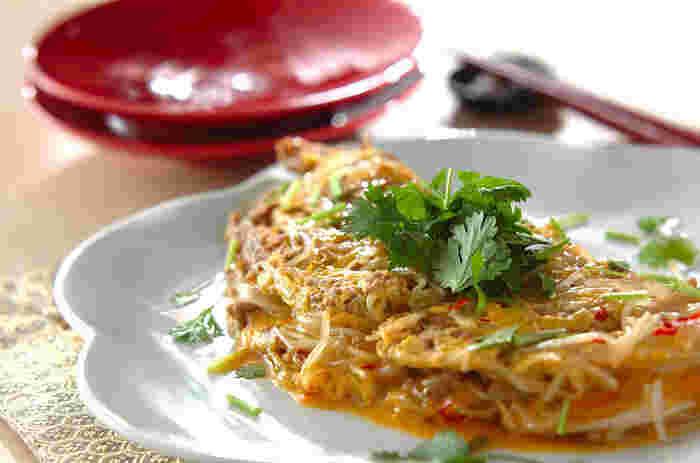 エスニック風のもやし入りオムレツです。  パクチーを添えて、本格的な味わいに。 唐辛子をちょっと加えて、くせになるようなピリ辛具合。  存在感あるもやし料理です。