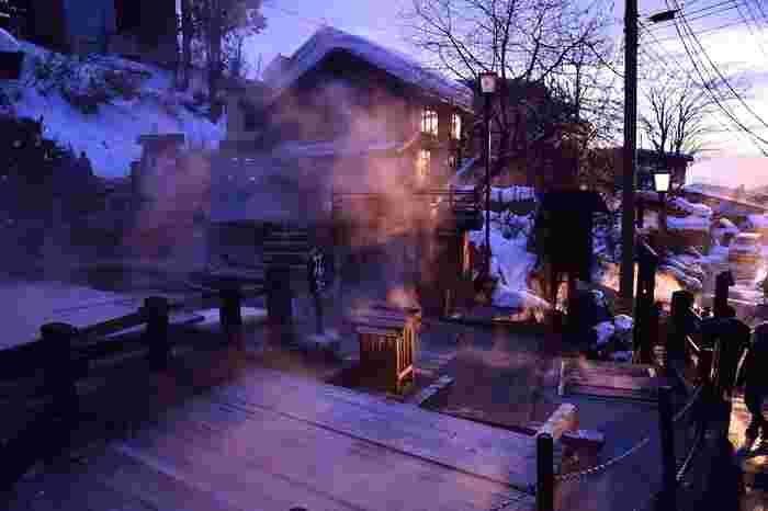 """日本で唯一、自治体の名前に""""温泉""""が入る野沢温泉村。この村にある「野沢温泉」は、古くから村民の暮らしと密接に関わりながら発展してきました。写真は野沢温泉の名所「麻釜(おがま)」。野沢温泉の源泉のひとつで、村民が野菜を茹でる台所としても親しまれています。"""