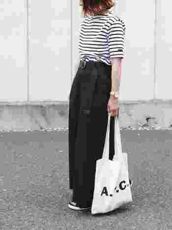 手提げで持つことでパンツの黒に白のキャンバスバッグの形がくっきりと映え、視線が下がることでラフな抜け感が出ます。