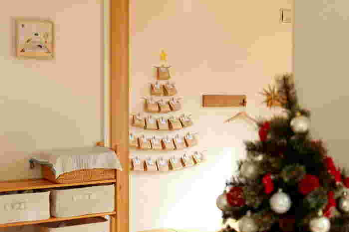 セリアの3つのアイテムで作ったアドベントカレンダー。クラフトバッグにお菓子を入れて、麻ひもにかけてガーランドのようにしています。クリスマスツリーの形にして、仕上げに一番上に星を飾りましょう。
