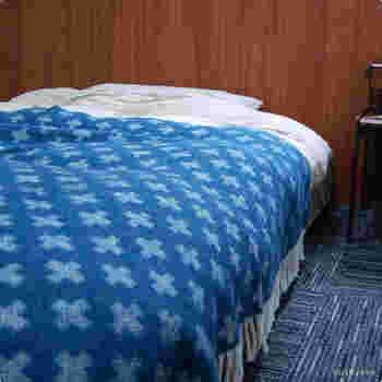 白をベースにしたベッドセットでも、こちらの画像のようなブランケットをかけるだけでも落ち着いた空間にコーディネートできます。青などの寒色は気分を落ち着かせるカラーとしても知られています。