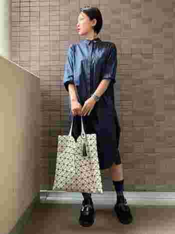 ネイビーのシャツワンピースには、ホワイトのバッグを合わせてモノトーンっぽい色のコーデに。ブルー系の花柄靴下とブラックのサンダルで、コーデに彩りとアクセントをプラス。