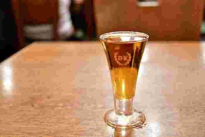 """""""あさくさの老舗酒場で生まれた歴史あるカクテル""""というのが、こちらの「電気ブラン」。ブランデーをベースにジンやワイン、キュラソー、薬草などが秘伝の分量でブレンドされているんです。誕生してから100年以上経っても謎に包まれているところが、小説の雰囲気に合いますよね。  アルコール度数が30度とかなり高いので、小説に登場する黒髪の乙女のようにお酒に強い人におすすめの一杯です。"""