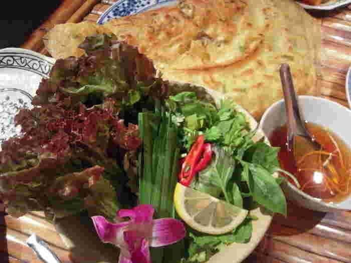 ベトナムのお好み焼き「バインセオ」をみんなでシェアしながら食べるのがおすすめ。パクチーなどの香草を巻きながら食べるのもおいしい。