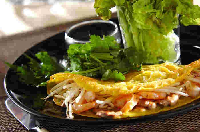 ベトナム風お好み焼きと呼ばれる「バインセオ」。米粉で作る皮は、ターメリックで鮮やかな黄色に。炒めたもやし、豚肉、海老をたっぷりと入れ、サニーレタスで包み、香菜を添えてつけダレを付けて頂きます。