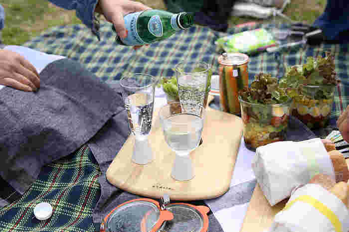 みんなのグラスをのせるアイディアも!土や草の上はレジャーシートを敷いても意外と不安定なので、こんな使い方もアリですね♪カッティングボードが1枚あるだけで、ピクニックが一段と素敵になりますよ。