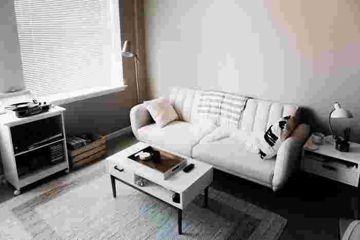 白のインテリアを基調としたお部屋。壁はほんのりグレージュがかっていて、それだけで落ち着いた雰囲気。ここにはソファに合わせて白のクッションを選びつつ、片方は黒の飾りも入った遊び心のあるものを追加するとよりお洒落なバランス感になります。