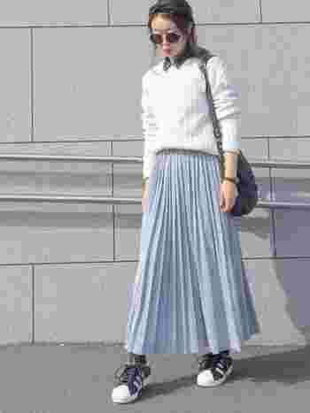 レディライクなプリーツスカートを、カジュアルに。白のニットの襟からちらりと覗かせたデニムシャツがポイントになっています。スニーカーを合わせれば、動きやすいきれいめカジュアルコーデの完成!