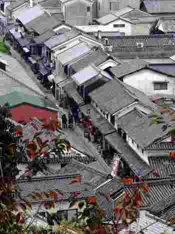 """""""本町通り""""・東町エリアは、小高い鶴形山(つるがたやま)の南方裾野に弧を描くように形成された、倉敷の発祥の地。江戸初期に新田開発で広がった集落が、物資の集散地として栄えるにしたがって、商家や庄屋、職人らの家々が建ち並び、現在の町の原型を形成しました。【画像は江戸から明治の面影を残す、町家や蔵が連なる""""本町通り""""。】"""