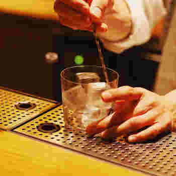 氷をグラスに入れ、バースプーンでステアします。入れる液体のストレスにならないよう、グラスを冷やして氷の温度に近づけてあげるイメージです。また、氷の溶けやすい角の部分を先に溶かしておくと、のちの工程での加水を抑えることができます。グラスが冷えたら溶けた氷の水をしっかりとグラスから切ってあげましょう。慣れてきたらバースプーンで氷を抑えながらで良いですが、難しい場合はトング等で抑えたほうがベターです。