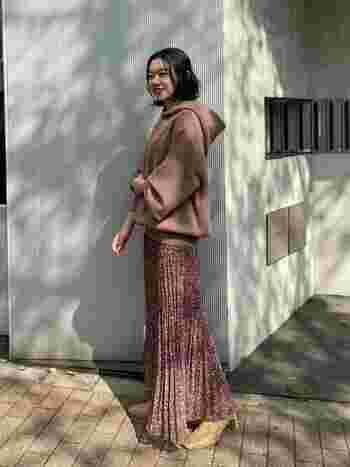 ピンクブラウン系の花柄スカートに、同系色のパーカーを合わせた着こなし。ロング丈のプリーツスカートはフェミニンな印象が強めですが、フーディーで上手にカジュアルダウンしています。ヒールのあるパンプスで、女性らしさもしっかりアピール。