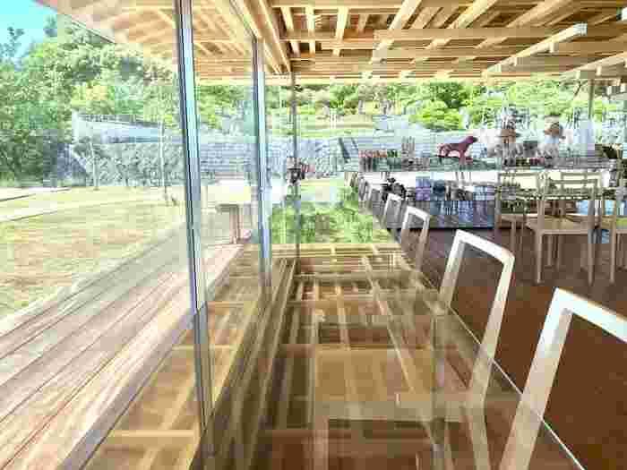 木のぬくもりを感じる店内。テラス席やデッキもあり、海を一望出来ます。さらに、周辺の緑や季節の花々も楽しめるなんとも贅沢な空間です。