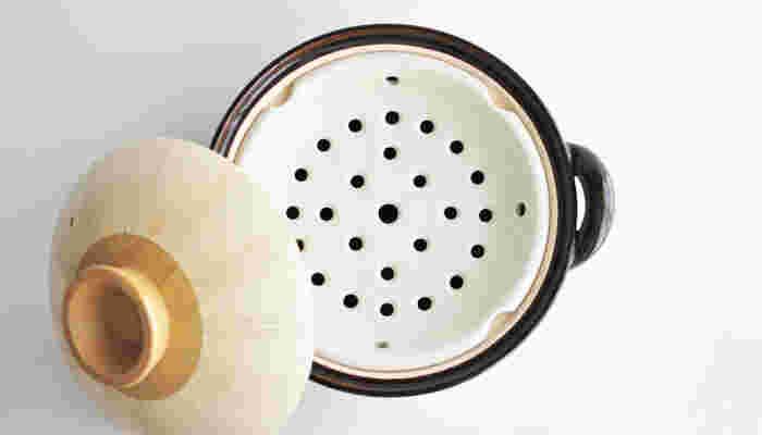 その穴の数や大きさ、位置にこだわった「陶製すのこ」がついた「ヘルシー蒸し鍋」は、鍋の深さ、卓上での目線など使い勝手の良さを追求した「万能土鍋」です。