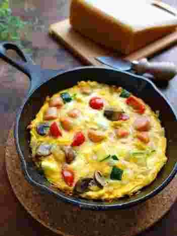 オープンオムレツは場が華やぐので持ち寄りパーティーにもおすすめ。具沢山のスペイン風オムレツは、野菜もたっぷりとれてヘルシーです。オーブンにそのまま入れられるフライパンでのレシピですが、オーブンを持っていなかったり、取っ手も直火OKなフライパンをお持ちでない方は、お皿でひっくり返し、フライパンで両面しっかり火を通しましょう。  【材料】 卵 2個 ソーセージ 2本 マッシュルーム・プチトマト 各2個 玉ねぎ・ズッキーニ 各1/4個 にんにく 1片 パルミジャーノ 10g 塩 ひとつまみ オリーブオイル 適量 胡椒 少々
