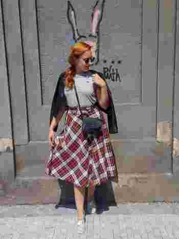 赤が印象的なタータンチェックのスカートを主役に、レザーのトップスを肩にかけて、ガーリーなロック風コーデに。足元をスニーカーにすれば、ハードすぎません。
