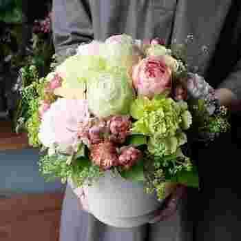 ピンク、グリーン、イエローなど、明るいトーンの花々をポップな雰囲気に仕上げたアレンジメントタイプのギフト。気分の上がる花々を、すべすべとした質感と優しい曲線が上品な花器と合わせています。アレンジメントはそのまま飾れるので便利◎  こちらも、ちょっとしたスペースでも飾りやすいMサイズと、お母さんへの感謝の気持ちを思いっきり表現できるLサイズの2つから選べます。