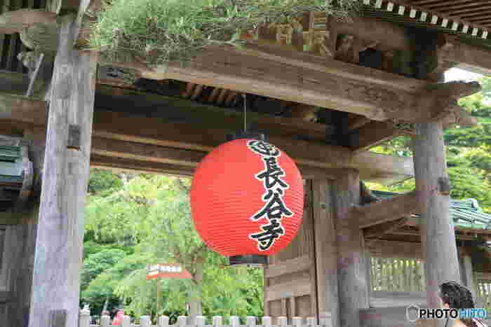 鎌倉駅から江ノ電で3つ目の駅、長谷にある長谷寺は、まず入り口の赤い提灯が印象的。写真などで見たことがある人も多いと思います。赤い提灯と、歴史を感じることが出来る扉や背景のグリーンとで、とてもいいコントラストです。