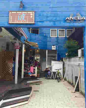 鎌倉駅東口より由比ヶ浜海岸方面にテクテク歩いて約10分。青い建物の奥に位置するのが「麺屋 波 WAVE」。