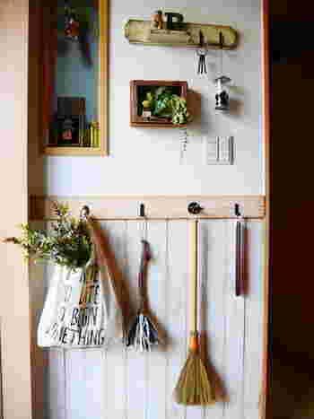 明るい玄関に無造作に投げ入れた草花と木の雑貨を飾って、気持ちのよい空間にしていますね。