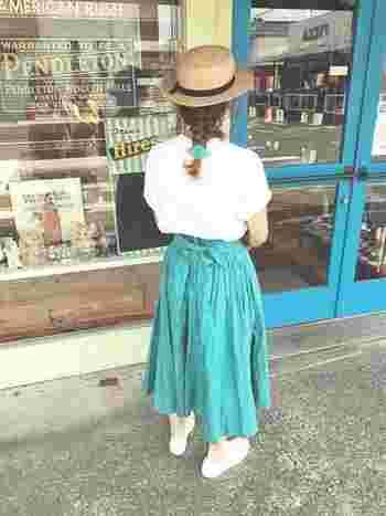 帽子をかぶる時には、低めの位置で束ねるとしっくり◎ スカートの色と合わせたシュシュで、後ろ姿まで可愛いコーデ♪