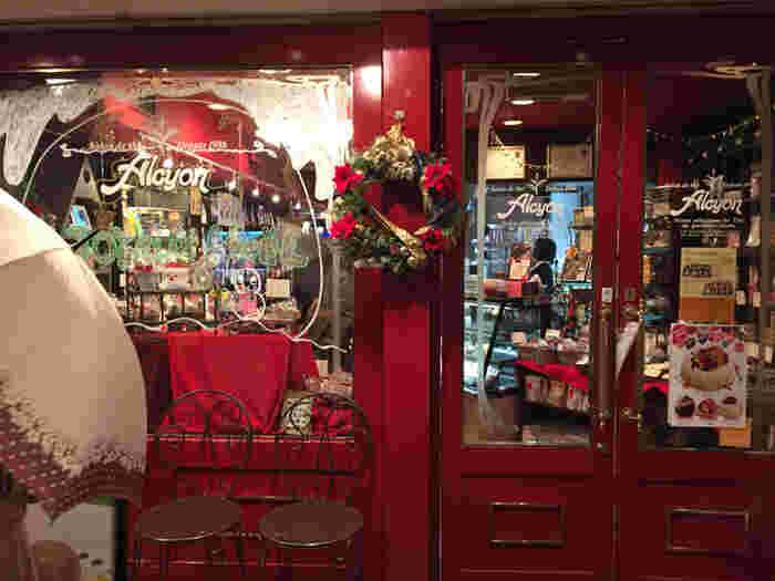 法善寺横丁という小粋な石畳の小道を抜けてすぐのところに「サロン・ド・テ・アルション」はあります。ぱっと目をひく赤い扉を開けると、そこには夢のようなケーキや色とりどりのマカロンが。