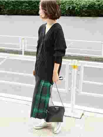ゆったりミドル丈の黒のVネックカーディガンに、緑のタータンチェックのスカートを合わせたトラッド風のカジュアルコーデ。旬のオーバーサイズは、袖をたくし上げたりラフに着こなすのがポイントです。